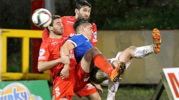 Portadown defenders Chris Ramsey and Ken Oman challenge Jimmy Callacher of Linfield