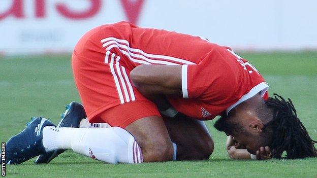 Wales captain and defender Ashley Williams holds his side in pain