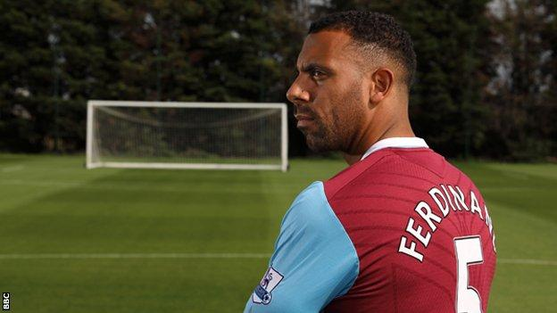 Anton Ferdinand stands on an empty pitch in a West Ham shirt
