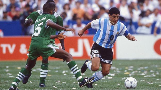Diego Maradona aleja el balón de Sunday Oliseh