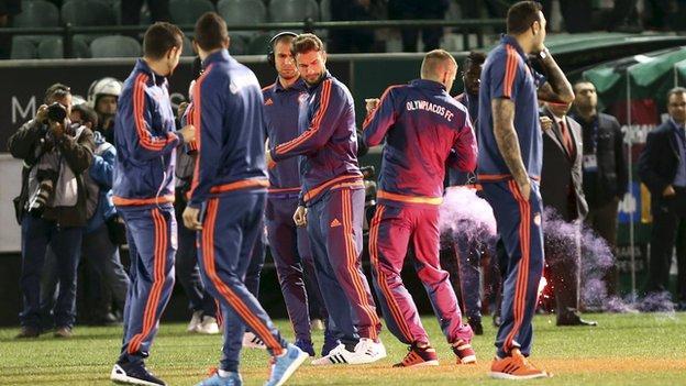 Olympiakos striker Alfred Finnbogason is hit by a flare