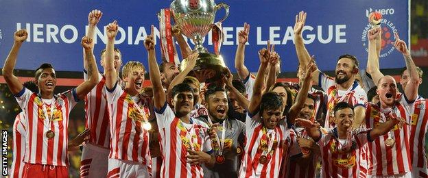 Atletico de Kolkata players celebrate with the trophy after winning the Indian Super League final match against Kerala Blasters FC