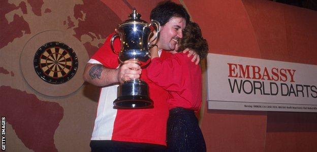 Phil Taylor (left) competing in the World Professional Darts Championship at the Lakeside Country Club at Frimley Green in January 1990