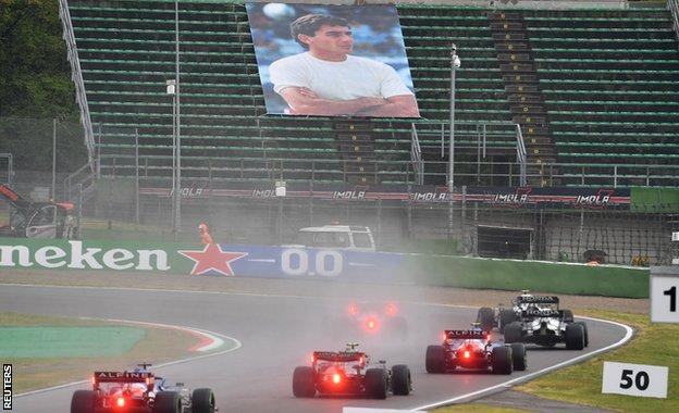 Drivers drive past a tribute to Ayrton Senna in the stands