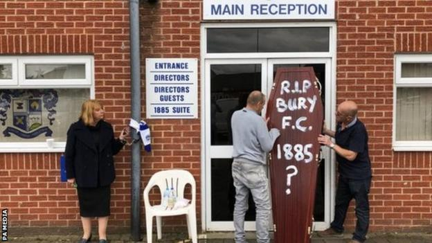 In one of the most evocative images of the downfall of Bury FC, Joy Hart chained herself to the stand which bears her father's name at their Gigg Lane home while fans later carried in a ceremonial coffin
