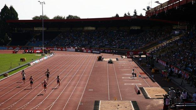 Athletes running on a track in front of a crowd
