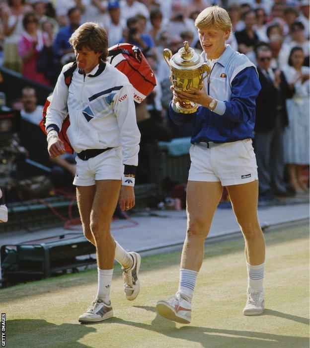 Boris Becker of Germany looks at the names engraved on the trophy as he walks off court with Kevin Curren after defeating him in the Men's Singles final of the Wimbledon Lawn Tennis Championship on 7 July 1985 at the All England Lawn Tennis and Croquet Club in Wimbledon in London, England.