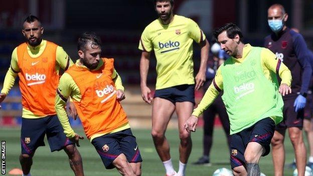 Barcelona superstar Lionel Messi (right) tries to take on team-mate Jordi Alba as the Spanish La Liga leaders step up their phased training