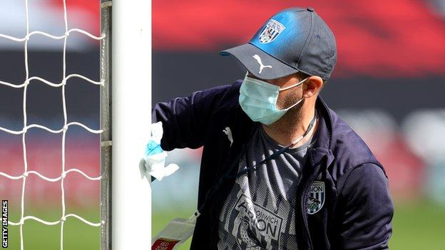 Ground staff disinfect the posts