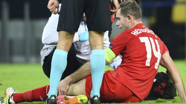 Jordan Henderson sits on the pitch after being injured