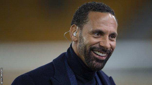 Rio Ferdinand smiling with a television earpiece in