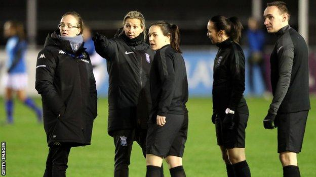 Carla Ward discussing pitch conditions with officials alongside Aston Villa head coach Gemma Davies before the postponed derby match earlier this month