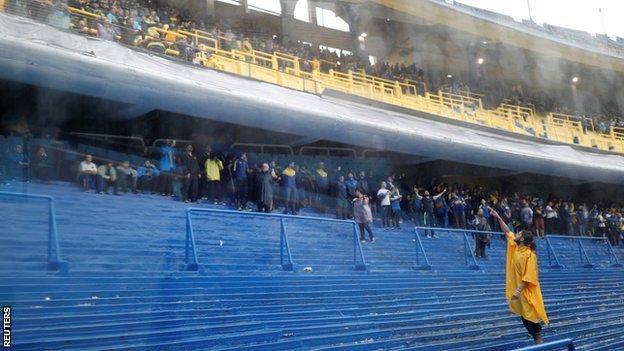 Fans shelter from the rain at Boca's La Bombonera stadium