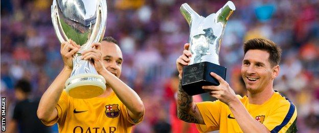 Andres Iniesta shows off the Uefa Super Cup and Lionel Messi the European player of the year trophy