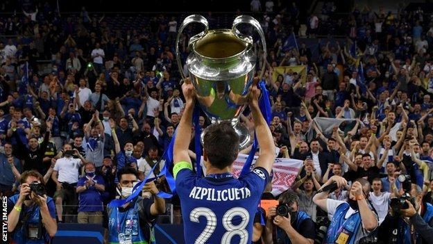 Cesar Azpilicueta holds the trophy up to the fans