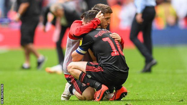 George Honeyman is consoled by a Sunderland team-mate