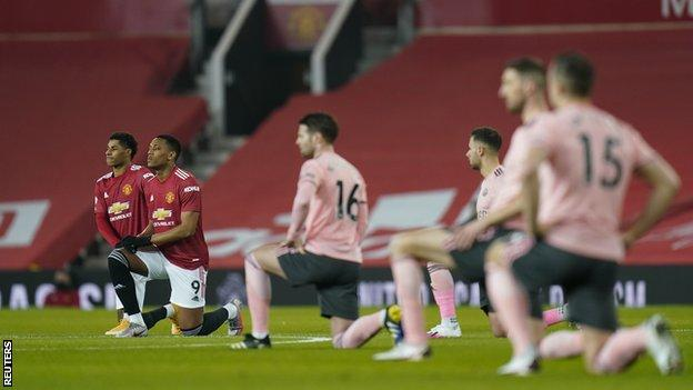 Manchester United and Sheffield United players kneeling before their Premier League game at Old Trafford