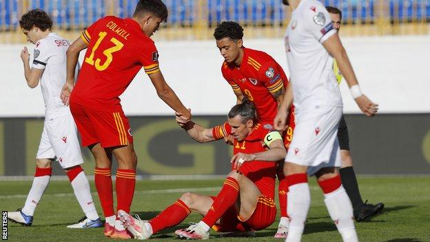 Wales skipper Gareth Bale is helped up after being fouled against Belarus