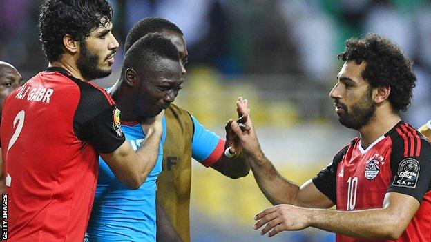 Burkina Faso's goalkeeper Herve Kouakou Koffi (centre) is consoled by Egypt's defender Ali Gabr and forward Mohamed Salah (R) after the 2017 Africa Cup of Nations semi-final in Gabon