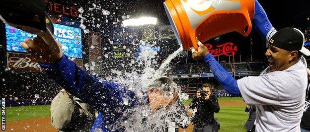 Manager Ned Yost gets a soaking from catcher Salvador Perez