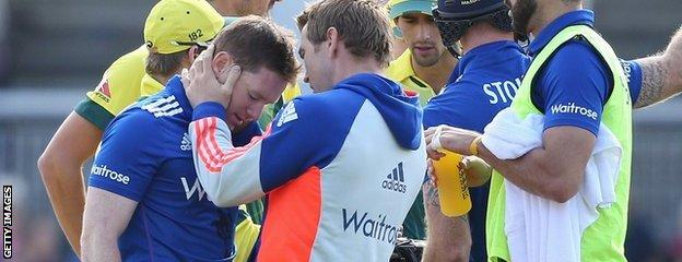 Eoin Morgan is checked over by the England physio
