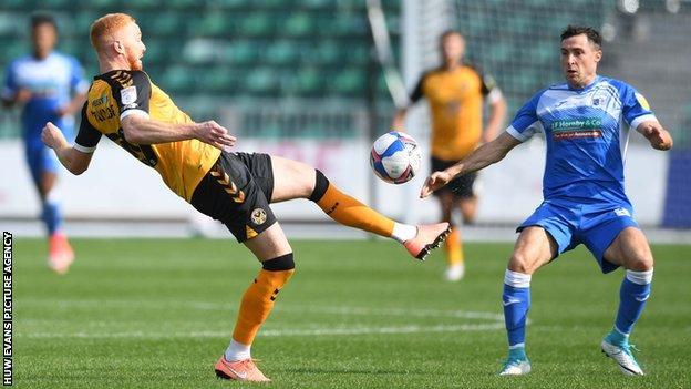 Newport's Ryan Taylor challenges Barrow's Mike Jones
