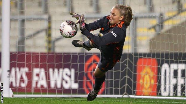 Manchester United's Emily Ramsey saves the shootout penalty by Manchester City's Laura Coombs