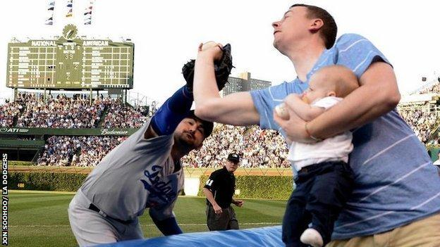 Father catches ball at Major League Baseball game with son in hand