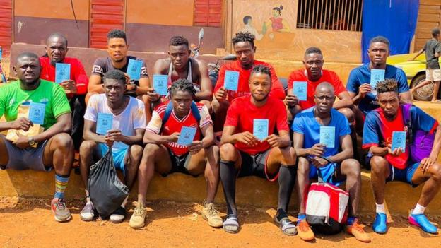 Players from Sierra Leone's Anti-Drugs Strikers FC with their Covid-19 vaccination cards