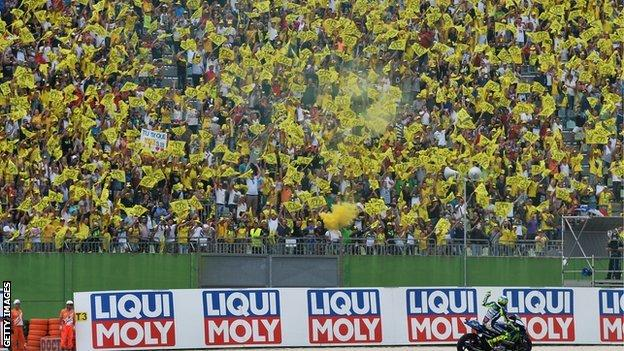 Valentino Rossi fans in the grandstands at a racetrack where they are holding yellow Rossi flags
