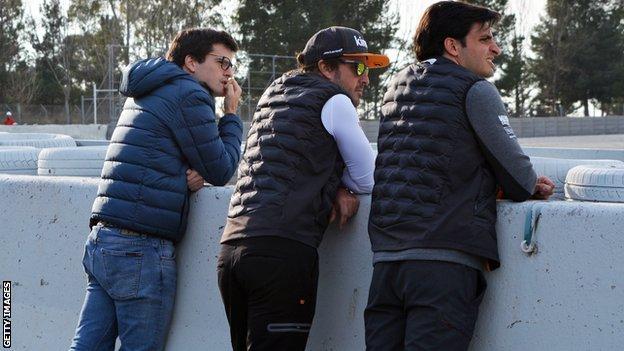 Fernando Alonso watches pre-season testing in Barcelona with McLaren driver Carlos Sainz