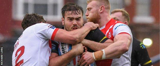 Widnes' Ted Chapelhow is wrapped up in a tackle against St Helens