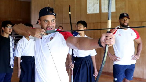 Jonathan Joseph (L) watched by team mate Joe Cokanasiga takes part in traditional Japanese archery, known as Kyudo, during the England team visit to Miyazaki Kita High