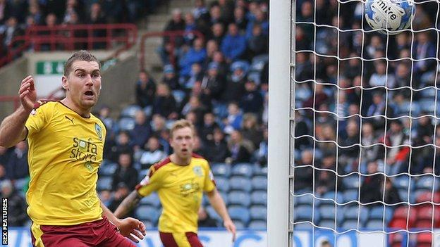 Sam Vokes watches as his the ball goes in off the post for Burnley's second against Huddersfield