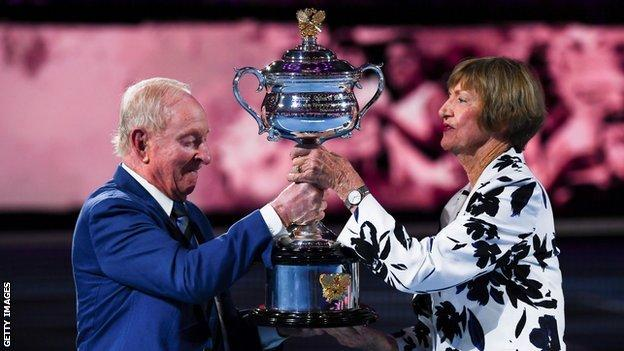 Rod Laver presents Margaret Court with a replica of the Australian Open trophy to commemorate 50 years since she won all four major titles in a calendar year