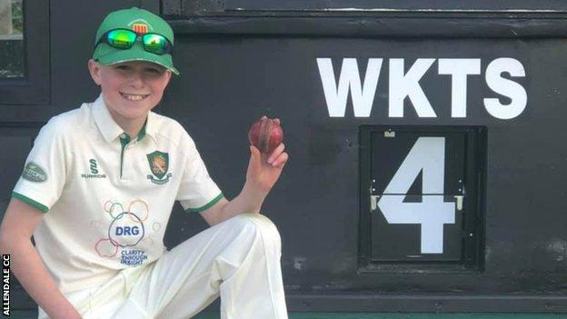 Owen Forbes holding the match ball in front of the scoreboard