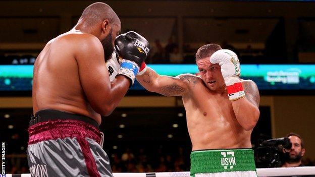 Ukrainian boxer Oleksandr Usyk (right) lands a punch on Chazz Witherspoon (left)
