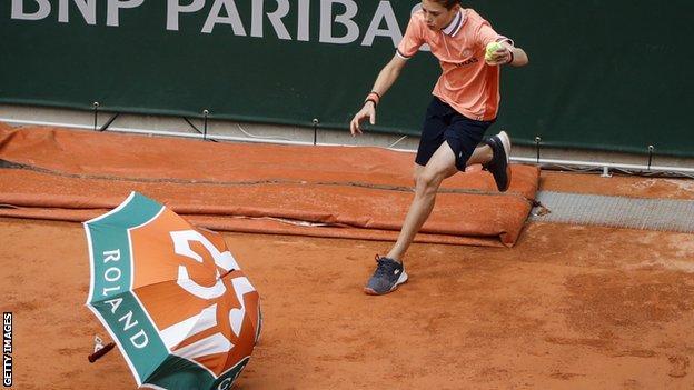 An umbrella blows onto the court