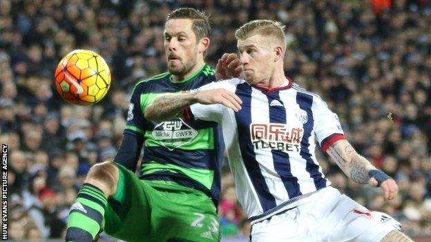 Gylfi Sigurdsson battles for the ball with James McClean