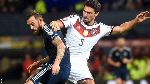 Steven Fletcher is tackled by Germany's Mats Hummels