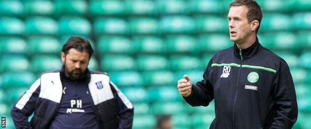Dundee manager Paul Hartley looks dejected, while Ronny Deila watches the action at Celtic Park