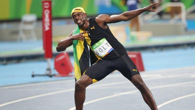 Usain Bolts celebrates with his signature lightning bolt pose