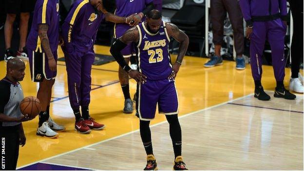 LeBron James looks at the floor with his hands on his hips following the LA Lakers' defeat
