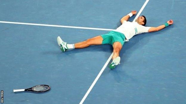 Novak Djokovic lays out on Rod Laver Arena after winning the 2021 Australian Open