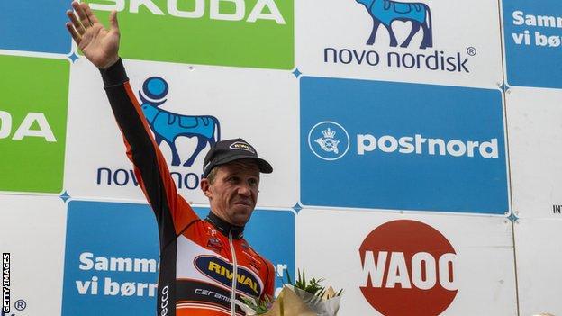 Chris Anker Sorensen waves on a podium