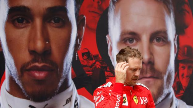 Sebastian Vettel walkes past a giant poster of Lewis Hamilton and Valtteri Bottas