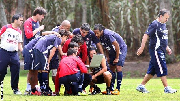 Members of the Chilean national football team huddle around a laptop as coach Marcelo Bielsa (R) walks away from the group during a training session at the Liga de Quito sports complex in Quito on October 8, 2008,. Chile will face Ecuador on October 12 in a FIFA World Cup South Africa-2010 qualifier match. AFP PHOTO/MARCO MUGA (Photo credit should read MARCO MUGA/AFP via Getty Images)