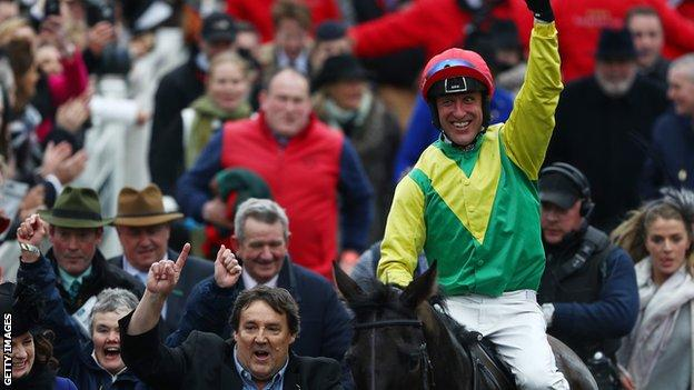 Jockey Robbie Power celebrates after steering Sizing John to victory in the Timico Cheltenham Gold Cup Chase during Gold Cup Day on day four of the Cheltenham Festival at Cheltenham Racecourse on March 17, 2017