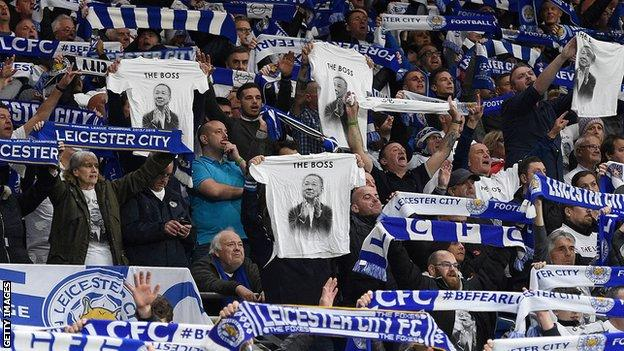 Leicester fans hold aloft t-shirts and scarves