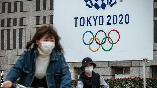 Cyclists wearing face masks with the Tokyo Olympic logo in the background